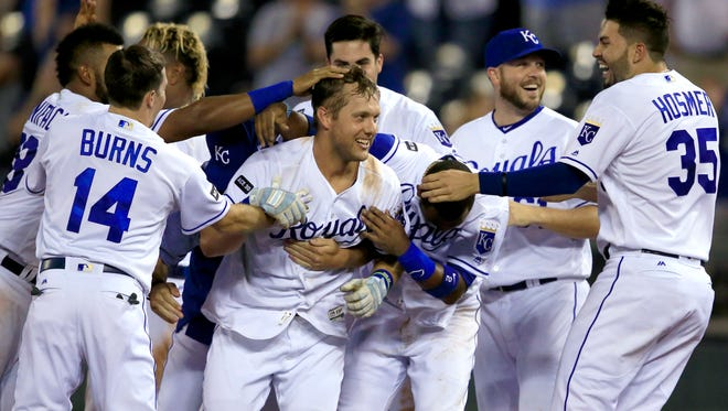 The Kansas City Royals' Alex Gordon, middle, is congratulated by teammates after driving in the winning run with a sacrifice fly during the ninth inning against the Detroit Tigers Wednesday night.