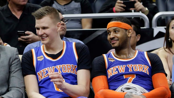 Knicks' Kristaps Porzingis, left, and Carmelo Anthony relax on the bench during the final moments of Wednesday's game against the Magic in Orlando, Fla. New York won 101-90. Porzingis scored a team-high 20 points while Anthony contributed 17.