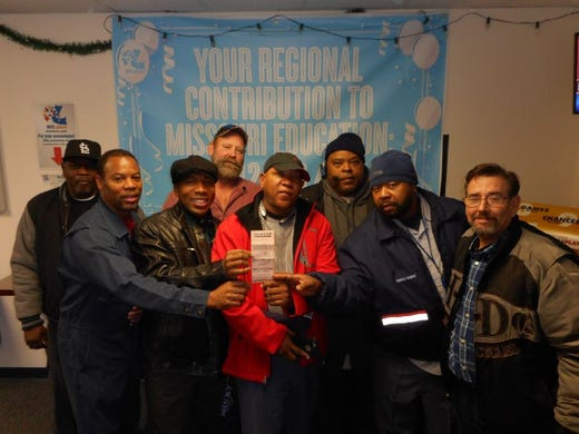 Postal workers hold up their winning lottery ticket.