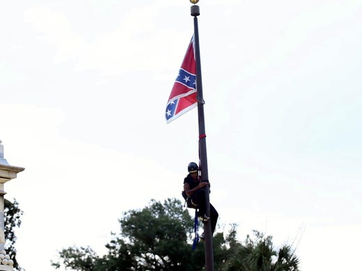 Activists take down the Confederate flag at the SC