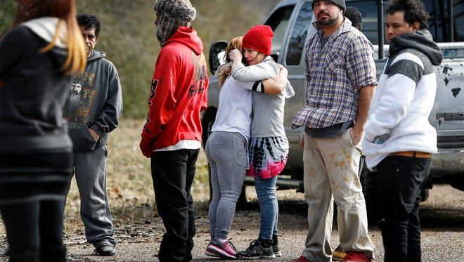 Bystanders embrace near the 5000 block of Belfast Drive where three people were found dead. Authorities believe carbon monoxide poisoning might be to blame. The three people, two adults and a 4-year-old child, were found by Memphis Light Gas & Water employees Friday morning.
