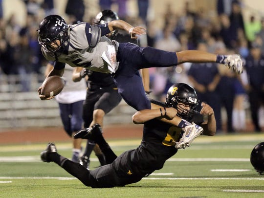Del Valle quarterback Raymond Montez tries to jump over Parkland linebacker Frank Kriegbaum on a quarterback keeper Friday at Parkland High School.