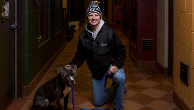 Neenah's Steve Callahan, here with a dog named Smokey at the Fox Valley Humane Association, volunteers as a dog walker.