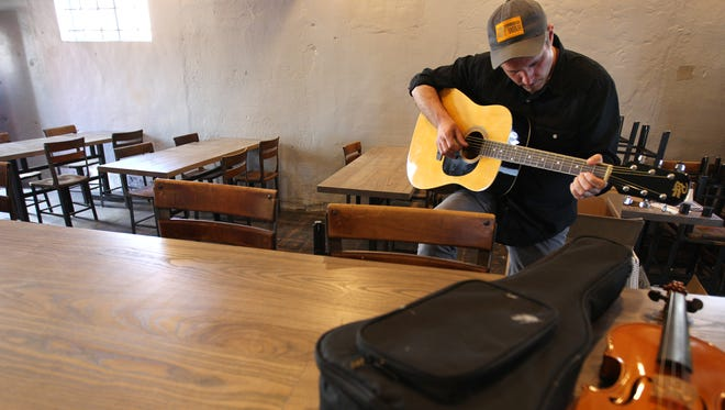 April 5, 2016 - Kevin Cubbins tunes a guitar inside Loflin Yard. (Mike Brown/The Commercial Appeal)