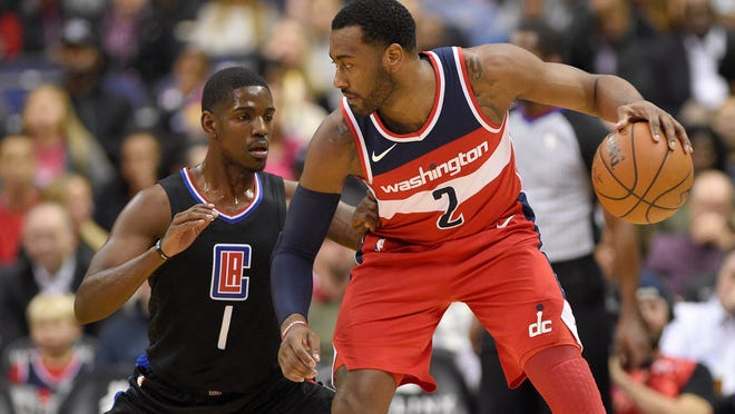 Washington Wizards guard John Wall (2) dribbles against Los Angeles Clippers guard Jawun Evans (1) during the first half of an NBA basketball game, Friday, Dec. 15, 2017, in Washington. (AP Photo/Nick Wass)