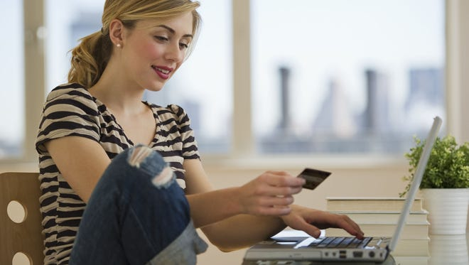Female with credit card shopping online from home.