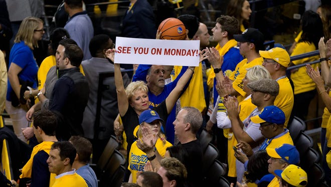 A Warriors fan holds up a sign during the final minutes of Game 5 of the Western conference finals against the Thunder.