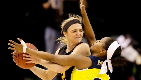 Iowa Hawkeyes guard Ally Disterhoft (2) looks to pass inside over Michigan Wolverines guard Siera Thompson (2) during the Big Ten women's tournament at Bankers Life Fieldhouse in Indianapolis on March 2, 2016.