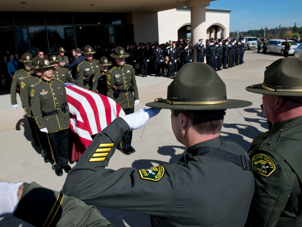 Placer Sheriff's Deputy Jeff Davis uses his left hand to  salute the casket of his comrade, Michael Davis Jr. whose casket is moved to a waiting hearse during a memorial service in Roseville, Calif. Jeff Davis was shot during the shooting rampage and