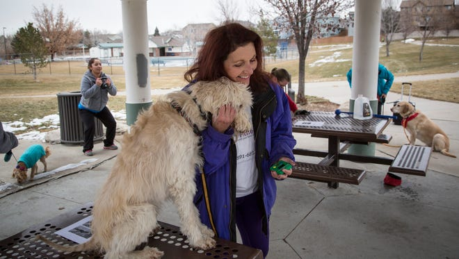 Isabel Chamberlin hugs her dog, Voodoo ,during her bootcamp class in Aurora, Colo. Chamberlin started Paws4Fitness, a dog exercise company, which she started after 40 years in sales.