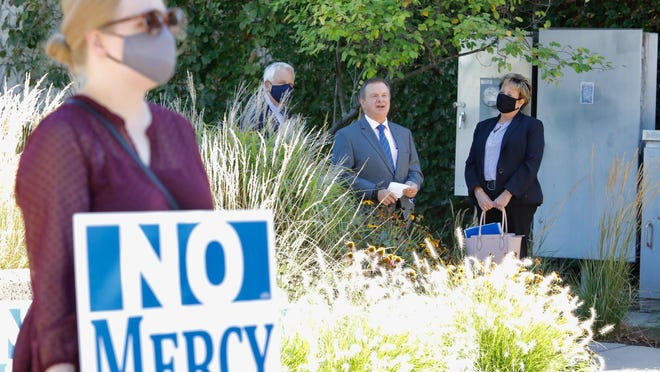Samantha Wagner, left, of Rockford, holds a sign protesting the closing of a mental health unit at Mercyhealth's Rockton Avenue hospital campus on Thursday, Sept. 3, 2020, as President and CEO of Mercyhealth Javon Bea, rear center, speaks with colleagues outside the Nordlof Center in Rockford.