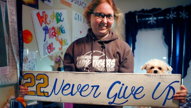 In this Dec. 8 photo, Lauren Hill holds a sign made for her, which she kept in her room, along with many other messages and gifts of support. Her dog, Sophie, is at her side.