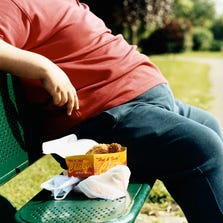 Mid-Section of an Overweight Man Sitting on a Park Bench With Take-Away Food