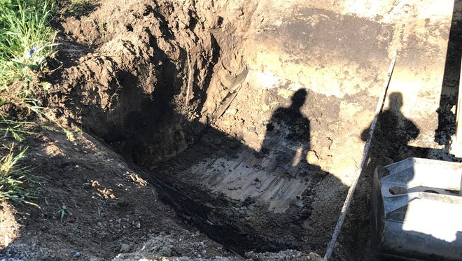 Crews excavate a sink hole Thursday morning on Tippecanoe County Road 700 South. The hole opened up Wednesday night after the all-day rain.