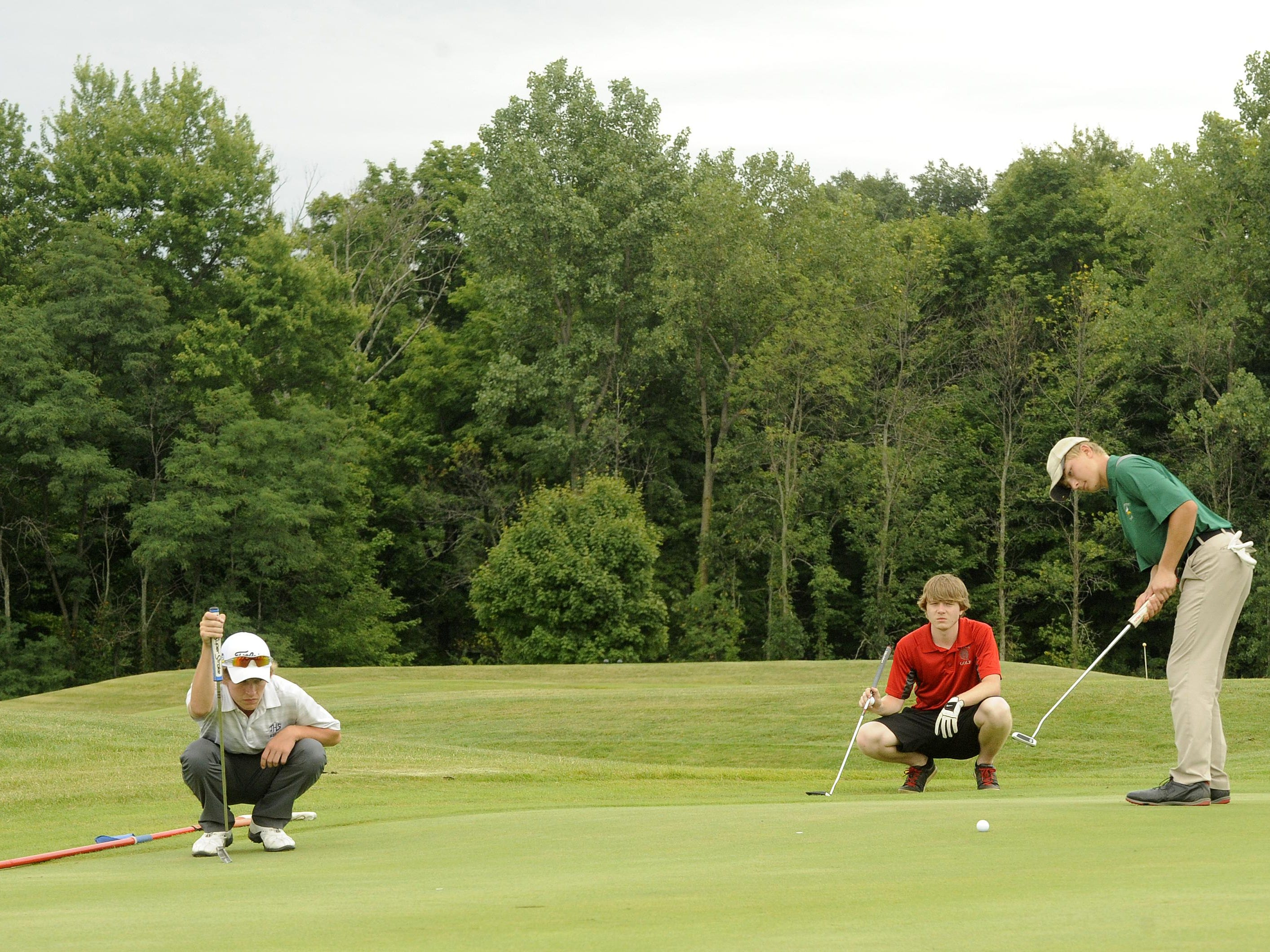 Johnstown's Jared Williams and Utica's Tyler Salyer read the green as Northridge's Jared Teeter putts on No. 18 during the Utica Invitational on Thursday at the Links at Echo Springs.