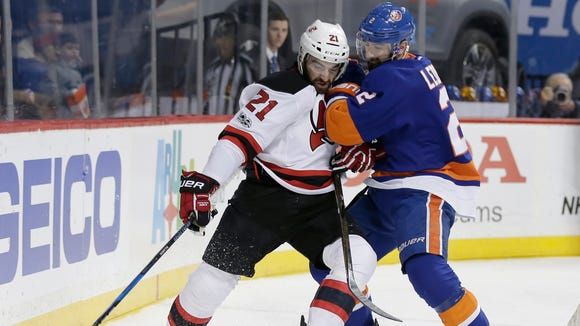 Devils' Kyle Palmieri (21) and Islanders' Nick Leddy (2) fight for control of the puck during the first period of a game Friday, March 31, 2017, in New York.