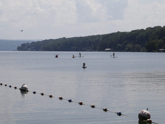 People on paddleboards and kayaks paddle on Cayuga