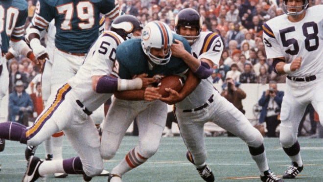 FILE - In this Jan. 13, 1974, file photo, Miami Dolphins' Larry Csonka drives between Minnesota Vikings' Jeff Siemon (50) and Paul Krause for one of his two touchdowns in the NFL football Super Bowl in Houston. Csonka was named MVP as Miami defeated the Vikings 24-7, becoming the first team since the Green Bay Packers to win consecutive Super Bowls. (AP Photo/File)