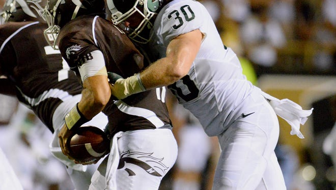 Riley Bullough (30) sacks WMU quarterback Zach Terrell during the fourth quarter of the Spartans 37-24 victory over the Broncos Friday, September 4, 2015, at Waldo Stadium in Kalamazoo.
