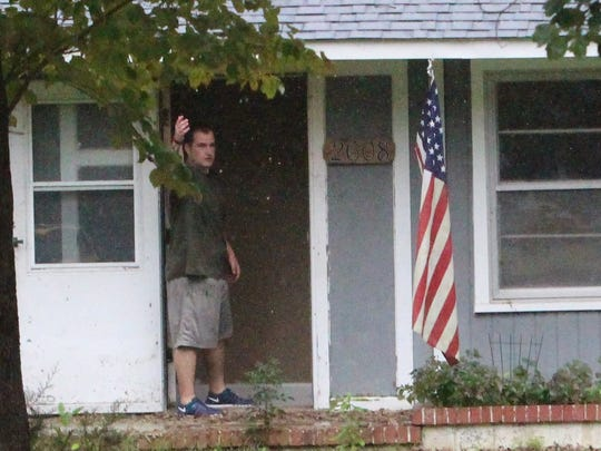 Caleb Keller directs officers inside a home he is working