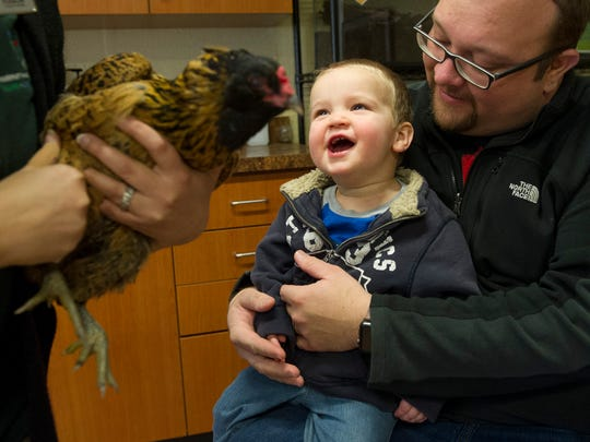 Chris Meyer, hold his son, Eli Meyer, 1, both of Newburgh, as he laughs during an Animal Encounter program at the Wesselman Woods Nature Preserve Nature Center in Evansville, Saturday, Jan. 28, 2017.