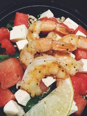Spoondrift's bowl of arugula and farro with watermelon and feta. The bowl is topped with gulf shrimp and lemon herb vinaigrette.