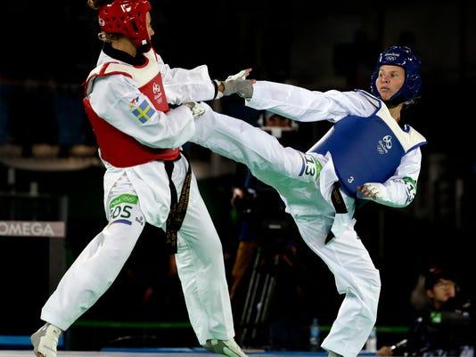 Suvi Mikkonen of Finland, right, and Nikita Glasnovic of Sweden compete in a women's Taekwondo 57-kg quarterfinal at the 2016 Summer Olympics in Rio de Janeiro, Brazil, Thursday, Aug. 18, 2016. (AP Photo/Andrew Medichini)