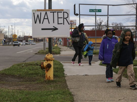 People walk along Saginaw St. on Flint's north side past a sign for water being given away at Mt. Calvary Missionary Baptist Church in Flint in March 2016. The church started handing out donated water from throughout the United States and Canada twice-a-week to people in need and small churches during the Flint water crisis.