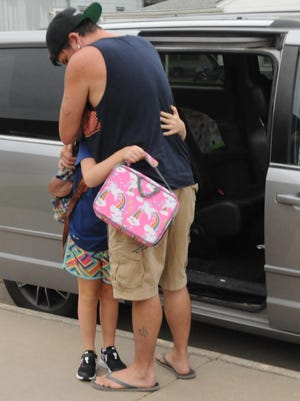 Tim Blackburn, of Salina, gives his third-grade daughter Rae Blackburn, 8, a big hug on the first day of school at Cottonwood Elementary on Monday morning.