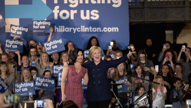 Democratic presidential candidate Hillary Clinton and musician Demi Lovato acknowledge the cheering crowd at a rally on the campus of University of Iowa in Iowa City, Iowa, on Thursday.
