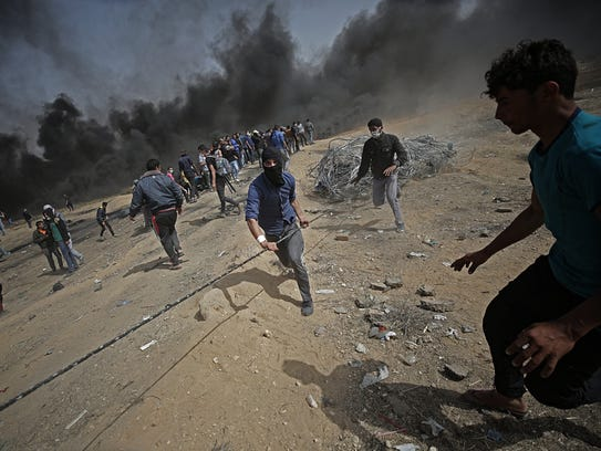 Palestinians protesters pull a barbed wire fence, installed