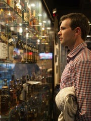 Patrick Stoess looks over the glass display case of bourbon at Down One Bourbon Bar in Louisvilloe.