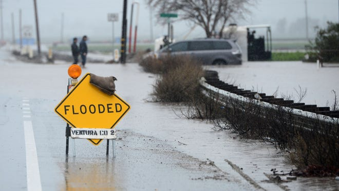 Zachary Belanger (left) and his father Cory Belanger watch flood water rise quickly around their van that stalled crossing Pleasant Valley Road in Camarillo on Sunday.