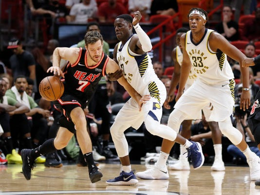 Miami Heat guard Goran Dragic (7) drives past Indiana Pacers guard Darren Collison and center Myles Turner (33) in the first quarter of an NBA basketball game, Sunday, Nov. 19, 2017, in Miami. (AP Photo/Joe Skipper)