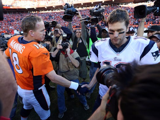 Denver Broncos quarterback Peyton Manning (18) and New England Patriots quarterback Tom Brady (12) shake hands after the 2013 AFC championship playoff football game at Sports Authority Field at Mile High.