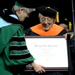 June Youatt, MSU Provost and Executive Vice President for Academic Affairs, left, and Stephen Hsu, vice president for research and graduate studies, present Charles Bachman with an orange College of Engineering stole during the honorary degree part of the advanced degree graduation ceremony at the Breslin Center Friday, December 18, 2015.