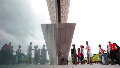 Visitors are seen reflected as they enter the Smithsonian National Museum of African American History and Cultural on the National Mall in Washington, Monday, May 1, 2017. The hottest ticket in Washington right now is for the new museum, where thousands of tickets are snapped up each month within minutes of being released, a full seven months after the museum opened.