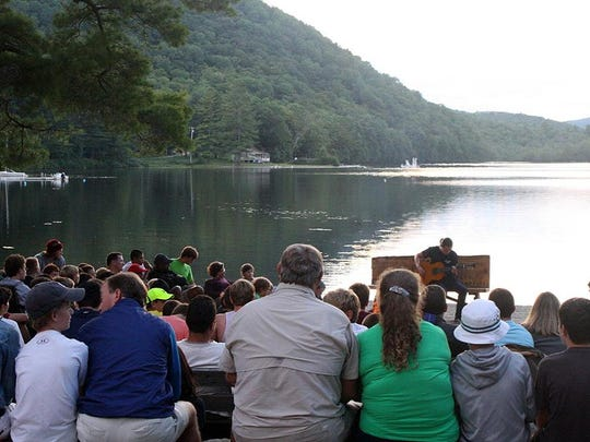 This Aug. 1, 2015 photo provided by Camp Pemigewassett in Wentworth, N.H., shows families listening to a guitarist by the lake at the camp on visiting weekend. Visiting days at summer camp can be challenging for families because reconnecting with parents in midsummer can rekindle campers' homesickness. Parents can make the experience stress-free by focusing on the child and camp activities, and by keeping their goodbyes short. (Dottie Reed/Camp Pemigewassett via AP)