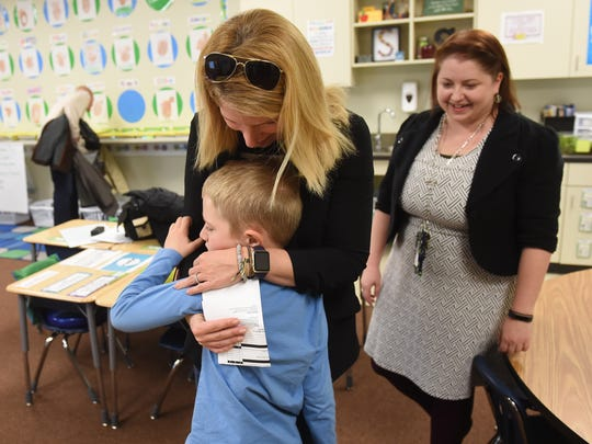 Jessica Brubaker embraces her son, York Academy second grader Sean Brubaker following his student run conference at the school.