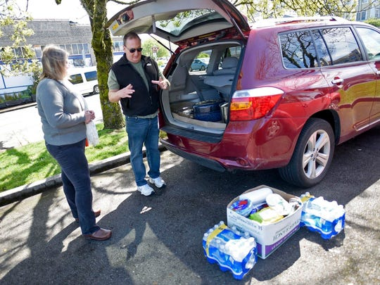 In this Wednesday May 3, 2017 photo, Mary Docherty, left, and Dan Marvin, right, unload food to help the less fortunate as part of their work with the Riverfolk non-profit group at People's Park in Astoria, Ore. The Riverfolk group has also been working with the area homeless population to help them obtain personal documents, such as identification and birth certificates that can help get them back on their feet.