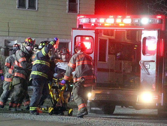 Rescue workers move Larry Hansen to an ambulance after