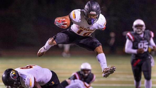 Tulare Union's Kazmeir Allen leaps over Tulare Union