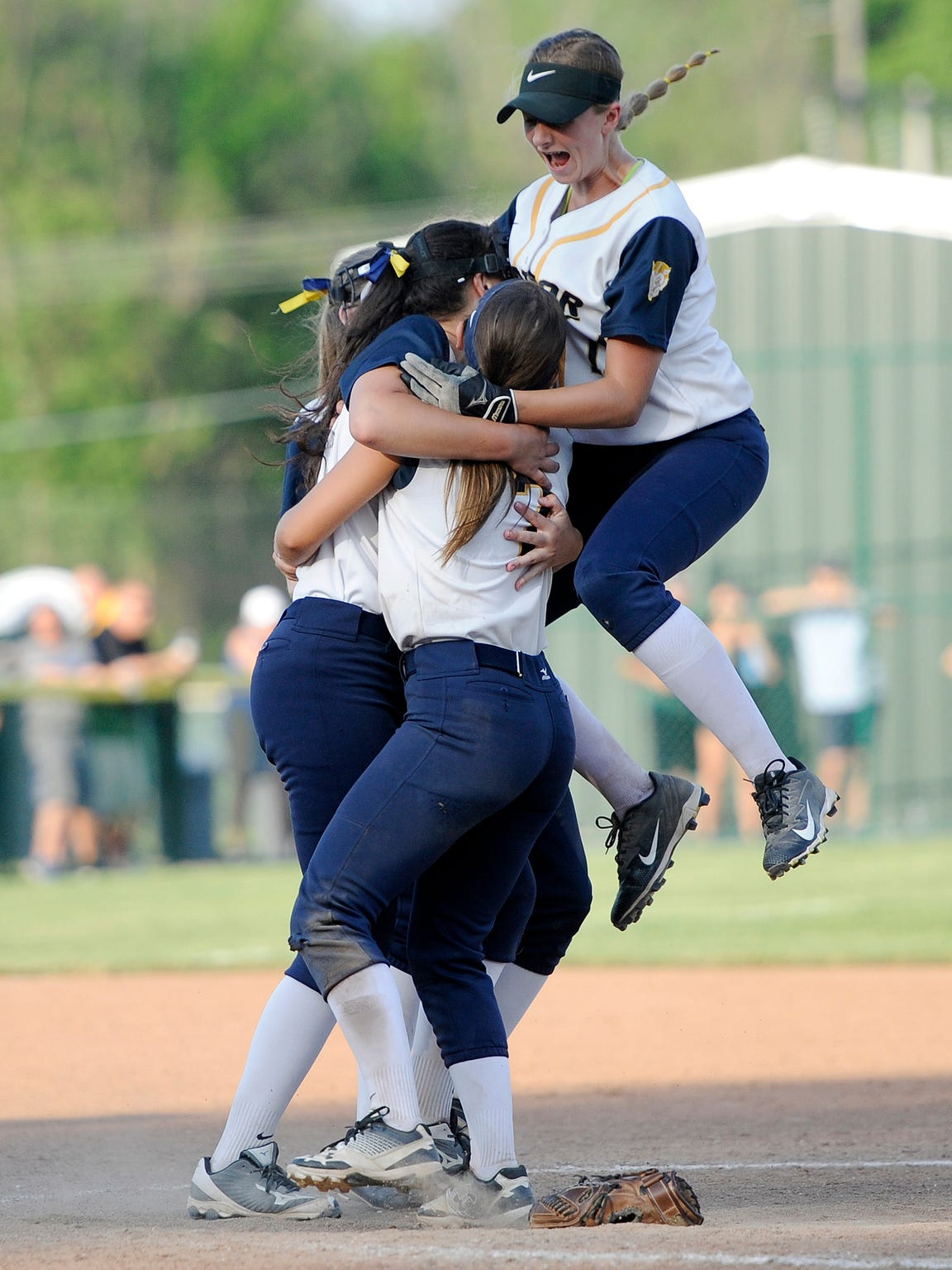 Victor's Emily Power, top, and teammates mob Katie Sidare after the final out to win the Section V Class AA championship game at SUNY Brockport, May 30, 2018. No. 1 seed Victor won the Class AA title with a 11-2 win over No. 2 seed Fairport.