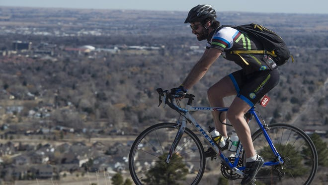 A cyclist travels on County Road 23 overlooking Fort Collins Friday, February 19, 2016.