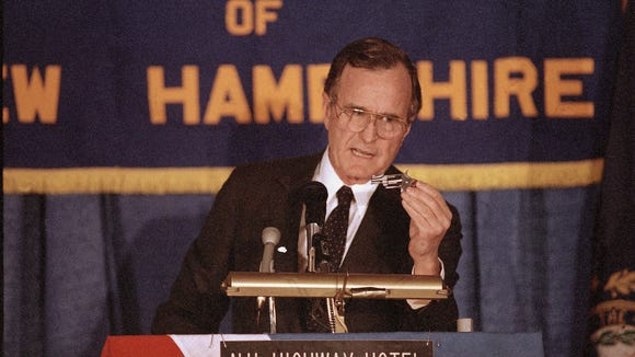 George H.W. Bush holds a pistol on Feb. 2, 1988, during