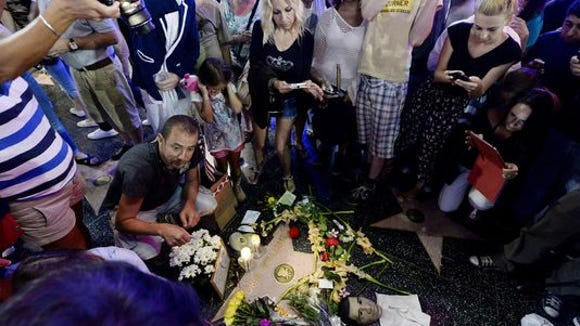 Flowers are placed in the memory of actor/comedian Robin Williams on his Walk of Fame star in the Hollywood District of Los Angeles, Monday, August 11, 2014.