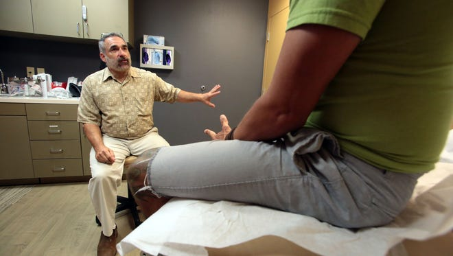 """Dr. David Hersh talks to a patient at the """"The DOCK"""" – a sexual-health clinic at the Desert AIDS Project about sexually transmitted diseases, including syphilis."""