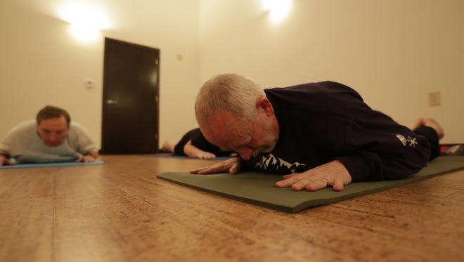 Tom Rau, 63, of Wausau, does yoga during a class March 3 at 5 Koshas Yoga & Wellness in Wausau.