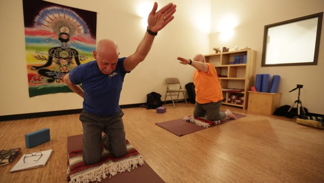 Yoga instructor Bill Miller works with a class March 3 at 5 Koshas Yoga & Wellness in Wausau.