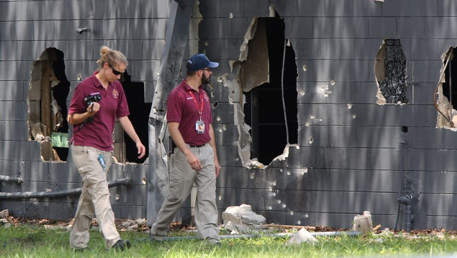 Investigators from the office of the medical examiner walk on the west side of Pulse nightclub where a gunman opened fire on early June 12, 2016, in Orlando.